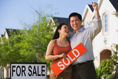 Asian couple holding Sold sign in front of house --- Image by © Terry Vine/Blend Images/Corbis